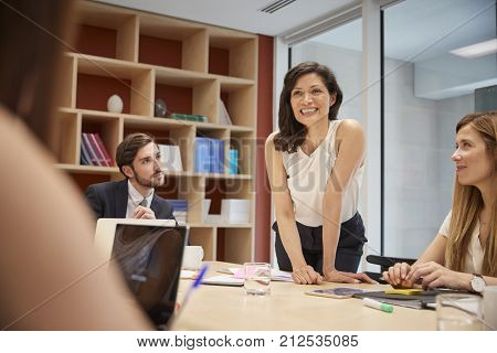 Female manager standing at boardroom meeting, close up