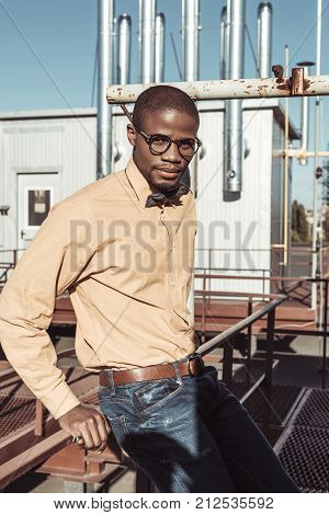 Stylish African American Man Sitting On Guardrails