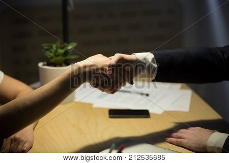 Two businesspeople shake hands to seal a deal, recruiter employing new staff member, human resources manager shaking hands with job candidate after interview. Close up side view. Handshake concept.