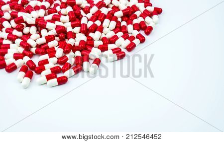 Red white antibiotic capsules pills on white background with copy space. Drug resistance antibiotic drug use with reasonable health policy and health insurance concept.
