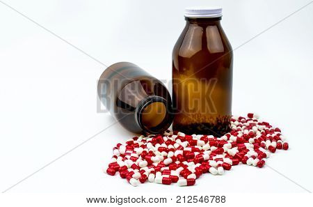 Colorful of antibiotic capsules pills with two amber glass bottles isolated on white background. Drug resistance antibiotic drug use with reasonable health policy and health insurance concept.