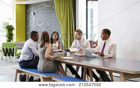 Five business colleagues in an informal meeting at work