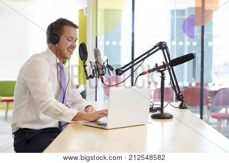 Happy young man recording a podcast, close up