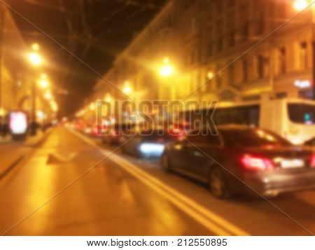 Abstract blur bokeh background at night. Blurred road with bokeh street of town and cars. Car parking with free space. Night light of traffic car on the city street