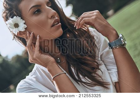 Beautiful as a flower. Attractive young woman keeping flower in hair and looking away while spending carefree time outdoors