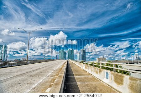 miami highway or public road roadway for transport vehicles and urban skyscrapers on cloudy blue sky background next to the port miami dade