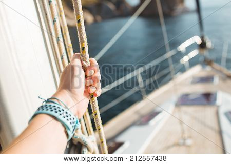 Woman hand on luxury yacht tackle. during the ocean voyage