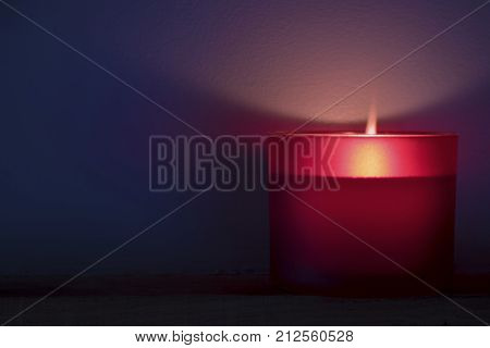 Single red lit scented candle with a flame glowing in dimmed space