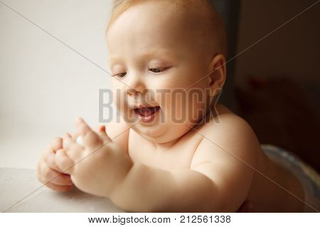 Innocent infant with perfect skin sits and holds one hand on window sill. Adorable newborn child with wide open mouth