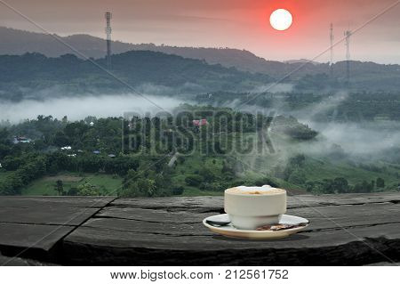 coffee shop in forest fog and coffee cup over wooden table misty mountains in the distance and sunset