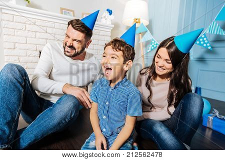 Uncontrollable laughter. Happy upbeat young family sitting on the floor and laughing hard while all of them wearing party hats and celebrating birthday