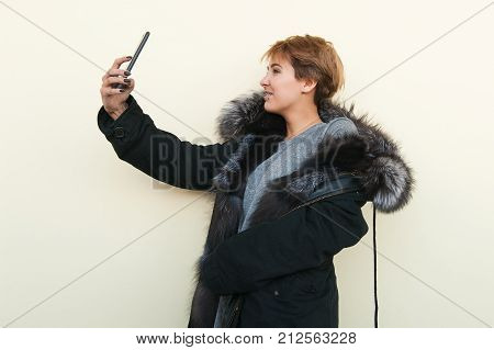 Happy girl in a fur coat doing selfie on smarphone. She is very happy.