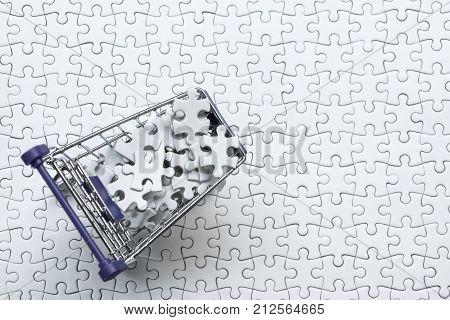Shopping cart full of jigsaw puzzle on white jigsaw puzzle backgruond Business solution concept key for success