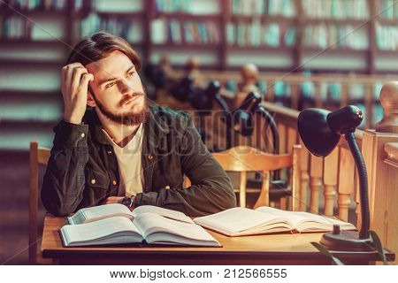 Portrait of thinking young bearded student man reading in a library hall on table with lot of books and lamp, indoor dusk time, education concept