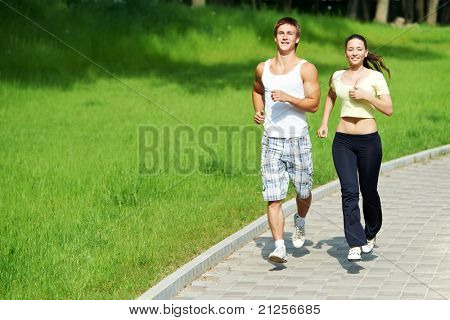 Young fitness couple of man and woman doing jogging sport outdoors