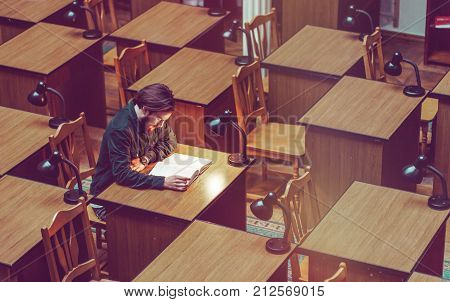 Young bearded student man reading in a library hall on table with lot of books and lamp, indoor dusk time, education concept
