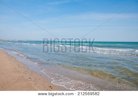Sea view. Blue water with waves sand beach under blue sky on sunny day