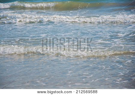 Nature background. Sea waves with white foam on sunny afternoon