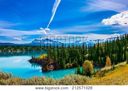 Turquoise Abraham Lake. In the blue sky silver trace of the plane. Rocky Mountains of Canada in the Indian summer. The concept of ecological and active tourism