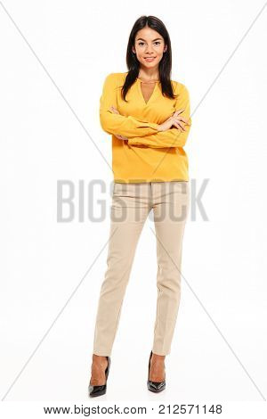 Full length portrait of an attractive confident woman standing with arms folded and looking at camera isolated over white background