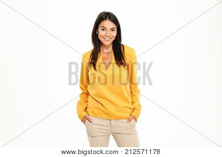 Portrait of a smiling young woman standing with arms in pockets and looking at camera isolated over white background