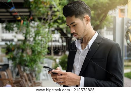 Young smart Asian businessman 20-30 years old checking business project and playing social media on mobile smartphone by 4g technolgy with copy space for text. Business concept.