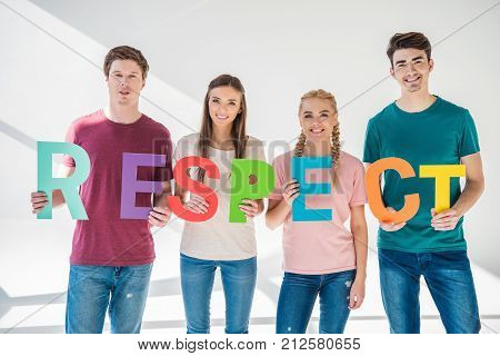 happy young friends holding colorful word respect and smiling at camera on grey