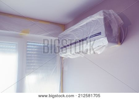 Air conditioner unit wrapped up in plastic sheet during home redecoration painting