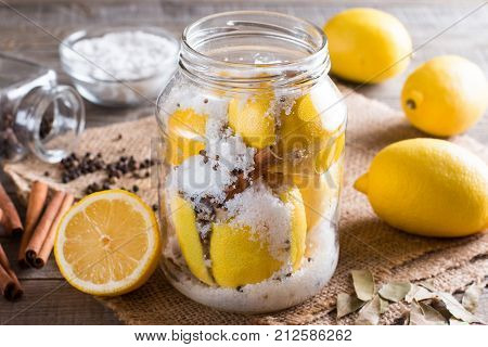 Preserved lemons with salt on a wooden board with lemon juice and spices