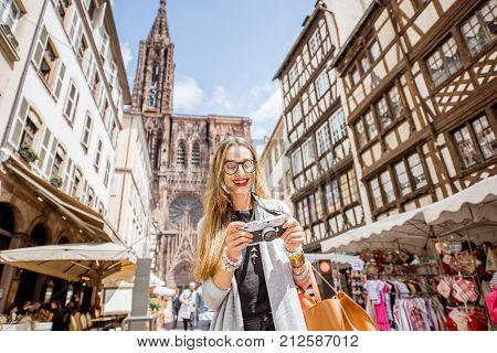 Young woman tourist standing with photo camera in front of the main cathedral traveling in Strasbourg city in France