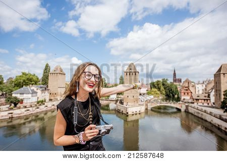 Portrait of a young woman tourist with photo camera on the beautiful landscape background with river and towers in the old town of Strassbourg city, France