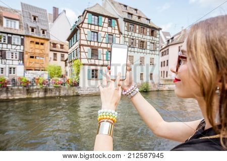 Woman holding phone with empty screen with beautiful old buildings and water chanal on the background in Strasbourg city in France