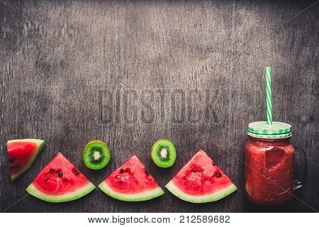 Watermelon fresh smoothie in glass jar, slices of watermelon on a dark wooden background. Top view. Copy space. Still life. Flat lay. Toned