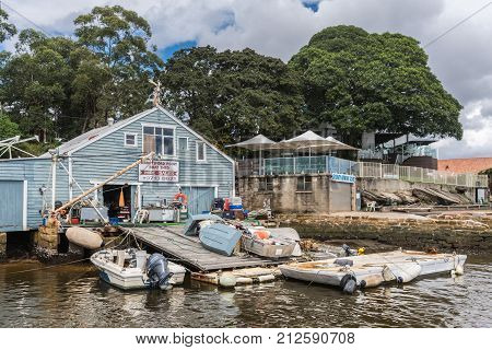Sydney Australia - March 24 2017: Wooden blue-painted Abbotsford boat repair and storage shop on shore with slipway along Parramatta River. Trashy boatyard with tools sloops workbench and more.