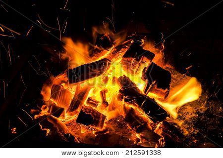 Abstract background with Burning firewood in the fireplace close up BBQ fire Sparking charcoal background. Spark of bonfire.