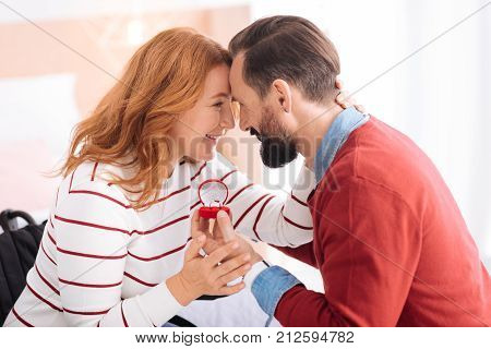 Lovey dovey. Bearded man proposing to a nice blond woman of middle age and she accepting his proposal and they looking at each other and smiling while he holding the ring