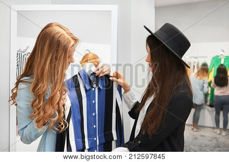 Professional shop assistant showing her female client a new dress in stock. Young stylish woman shopping at the mall service communication advice people lifestyle purchasing salesperson sale discount.