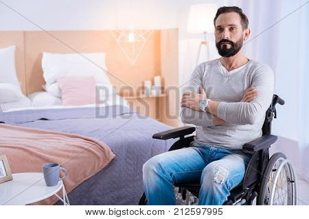 In the blues. Serious bearded dark-haired disabled man of middle age wearing a white shirt and a watch and having his hands crossed while sitting in a wheelchair