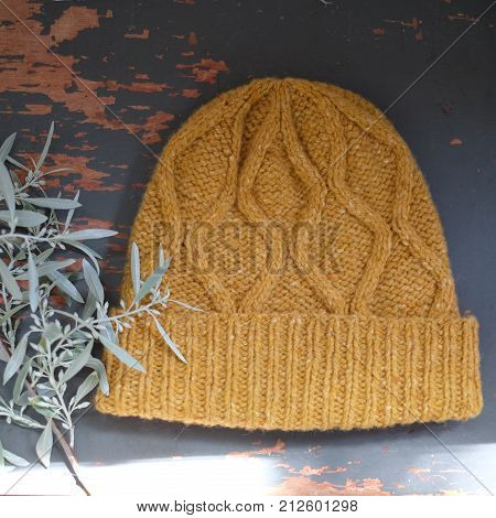 Orange knitted cap of wool on a wooden background