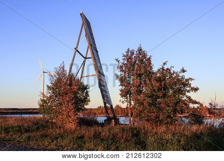 Huge navigation mark, trees and power plant. Red rowan, bushes in evening lit. Windmill in the background.