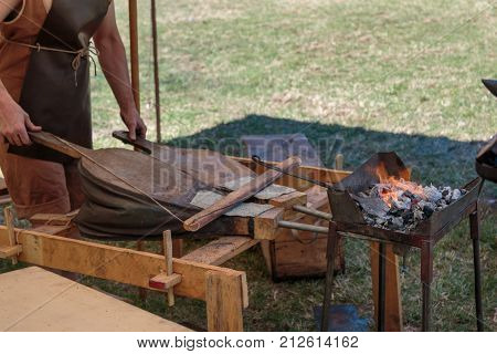 Blacksmith Blows Coals with Bellows, Working Tool.
