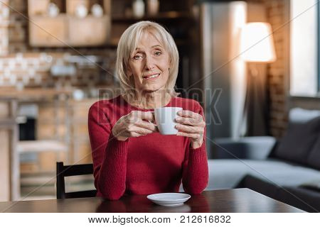Baby boomer. Peaceful calm aged woman sitting at the table and looking glad while holding a cup of tea