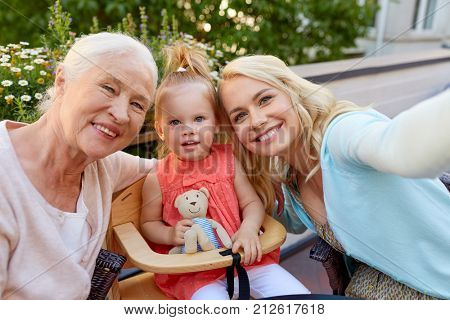family, generation and people concept - happy mother, daughter and grandmother taking selfie at cafe or restaurant terrace