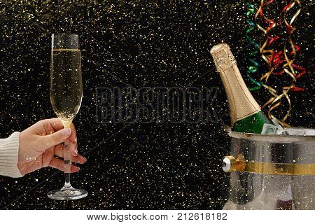 Celebrating new year, birthday, xmas party. Bottle of champagne in a bucket, female hand with flute and colorful tinsel on black backgroud with golden glitters, copy space. Mockup for postcard