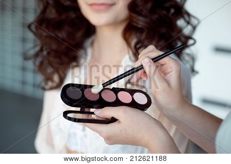 Makeup artist applies eye shadow. Perfect smooth skin.Applying makeup. Application of shadows on the model's eyes.