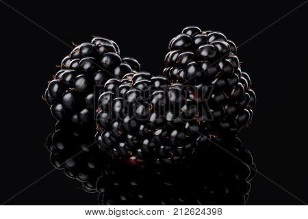 Three large ripe blackberry berries lie on a black glossy surface