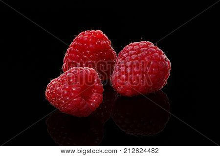 Three berry of raspberries on a black background close-up