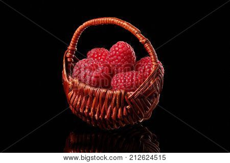 A small basket with raspberries stands on a black glossy background