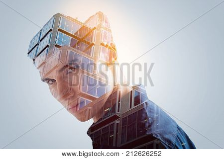 Original thinking. Double exposure  of modern architecture engineering and inviting irresistible hot guy gazing at the camera posing against the grey background