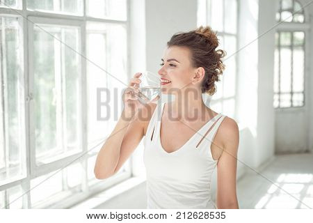 Portrait of a beautiful young woman with a healthy lifestyle smiling while drinking a glass of plain water indoors